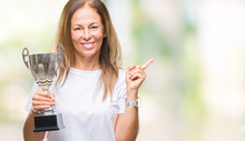 Middle Age Hispanic Winner Woman Celebrating Award Holding Trophy Over Isolated Background Very Happy Pointing With Hand And Finger To The Side