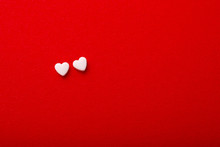Two White Heart Shaped Pills On Red Background. Minimalism. Copy Space