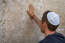 Man Hand And Pray Paper On The Western Wall, Wailing Wall The Place Of Weeping Is An Ancient Limestone Wall In The Old City Of Jerusalem. Second Jewish Temple By Herod The Great.