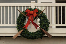 Nautical Wreath With Old Worn Oars And Sparkly Red Bow Mounted On Wooden Porch - Closeup
