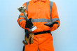 Best builder contractor award concept. Golden cup trophy in the worker hands isolated on blue background.