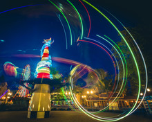 Light Trails Of Carousels In Amusement Park At Twilight