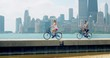 Couple Bikes Across Beach, Chicago Skyline Behind