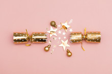 Christmas Crackers. Luxury Gold Festive Cracker On A Pastel Pink Background