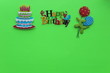 canvas print picture - happy birthday written with different colors with a cake candles and balloons on a green background with writing space