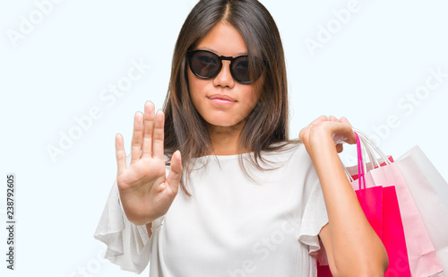 Valokuva  Young asian woman holding shopping bags on sales over isolated background with o