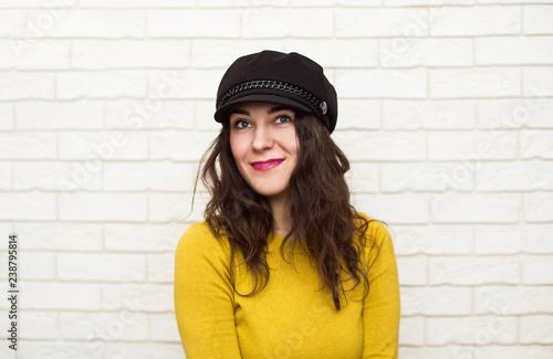 Fotografía  Portrait of a brunette in a hat on a light background
