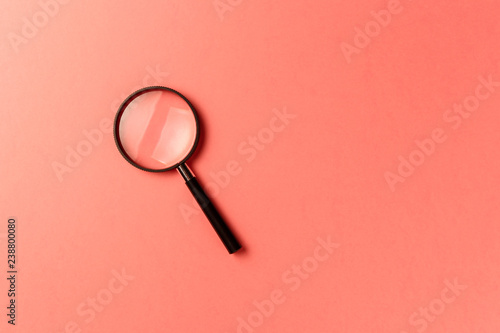 Photo  Magnifying glass on coral background