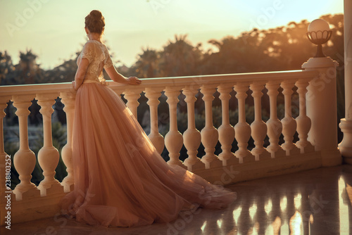 Fotografie, Obraz  Beautiful lady in luxurious ballroom dress with tulle skirt and lacy top standing on the large balcony looking away at sunset