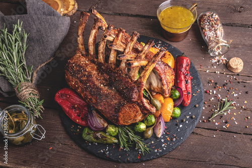 Grilled roasted rack of lamb veal chops with vegetables, on a wooden surface