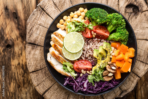 Buddha bowl salad with chicken fillet, brown rice, avocado, pepper, tomato, broccoli, red cabbage, chickpea, fresh lettuce salad, pine nuts and walnuts. healthy food. balanced diet eating. Top view