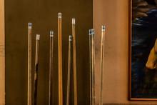 A Group Of Billiard Cue Sticks Near A Wall.