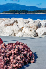 Close-up On Pink Fishing Net With Buoys Piled And Drying Near The Water Edge At The Port Of Corfu, Kerkyra Island, Greece In A Bright Sunny Spring Day Near Protective Wall Of Stones