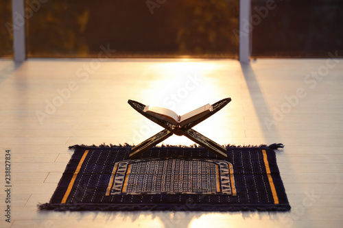 Rehal with open Quran on Muslim prayer mat indoors