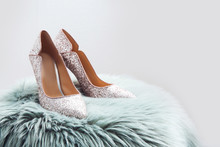 Stylish Female Shoes On Fur Against Light Background. Space For Text