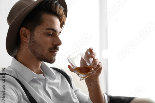 Young man with glass of whiskey at home. Space for text