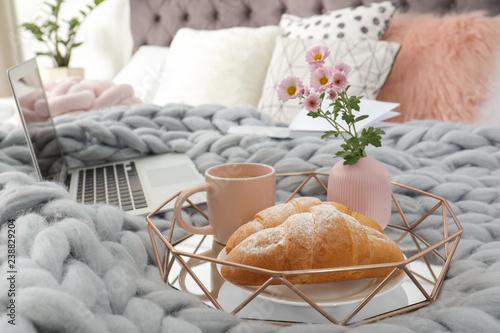 Fototapeta Tray with tasty breakfast and laptop on bed obraz