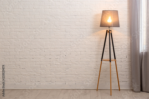 Photo Modern floor lamp against brick wall indoors. Space for text