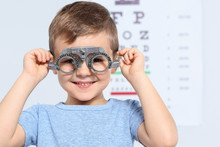 Little Boy With Trial Frame Near Eye Chart In Hospital, Space For Text. Visiting Children's Doctor