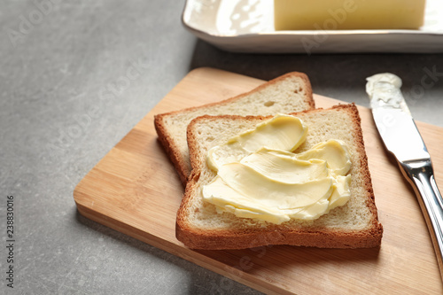 Tasty bread with butter and knife on wooden board