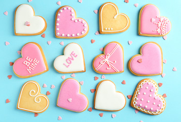 Composition with decorated heart shaped cookies on color background, top view. Valentine's day treat