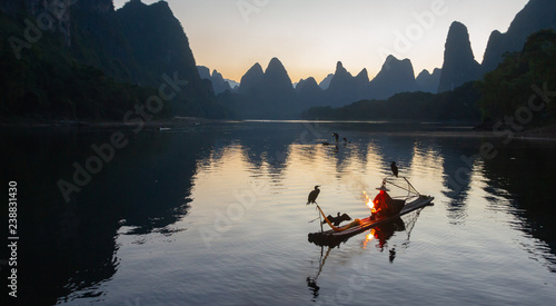 Photo Cormorant fisherman on raft in lake in Guilin, China, with three cormorant birds