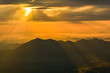 landscape sunrise on hill mountain with rays of sunlight shining on the cloud yellow sky