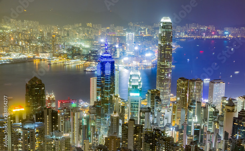 Hong-Kong Hong Kong skyline at night as seen from Victoria Peak. Illuminated skyscrapers in foreground, Hong Kong harbor in background.
