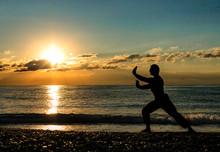 Man Practising Wushu At Sunset. Silhouette Of A Man On Sunset