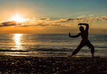 Man Practising Wushu At Sunset. Silhouette Of A Man On Sunset