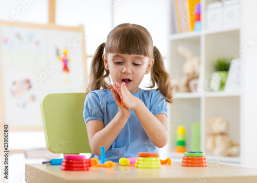 cute little girl playing with plasticine