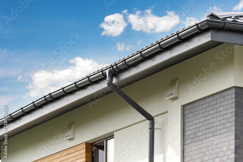 Valokuvatapetti Photo of black rain gutter pipe on white wall under rood of new comfort house wi