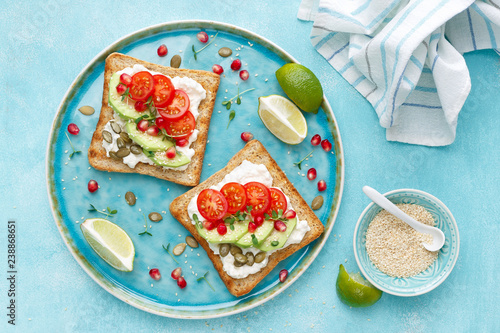 Toasts with feta cheese, tomatoes, avocado, pomegranate, pumpkin seeds and flaxseed sprouts. Diet breakfast. Delicious and healthy food. Flat lay. Top view