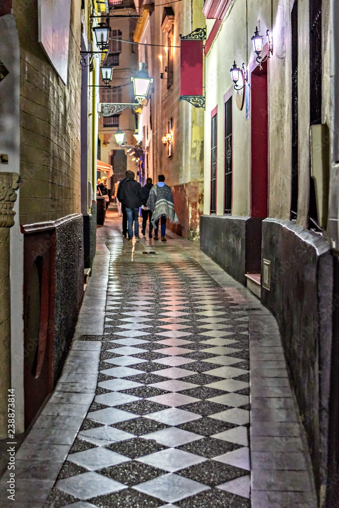 Narrow street in old town Seville, Spain, at night.