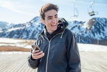 Cheerful Guy With Smartphone On Ski Resort