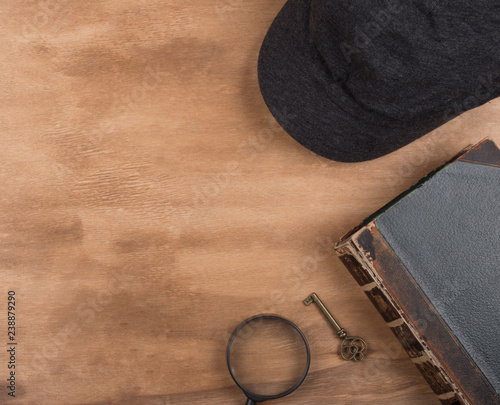 Fotografía  Cap of a detective, an old book, a key and a magnifying glass against a worn woo