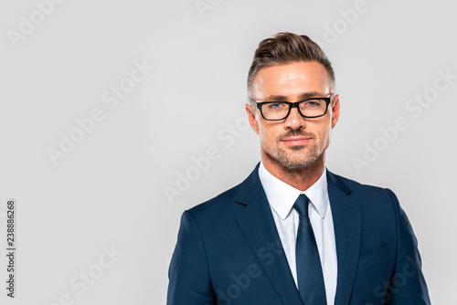 portrait of handsome businessman in suit and glasses looking at camera isolated on white