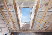 Mansard With Environmentally Friendly And Energy Efficient Skylight Window Against Blue Sky. Room Under Construction With Wooden Beams, Boards And Windows