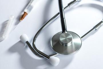 stethoscope on white table with syringe