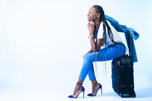 A Woman Is Sitting On A Suitcase. Black Girl Traveler. Moving To Another Country. Emigration. African Girl Thinking About Emigration. Cheerful Look. Tourist. The Girl Thinks About The Future.