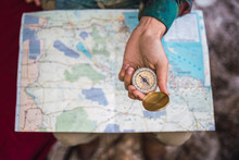 Hand Holding Compass Over Map