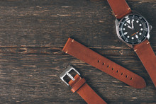 Brown Leather Handmade Watch Strap On Mens Luxury Watch Laying On Dark Rustic Wooden Table. Close Up. Copy Space.