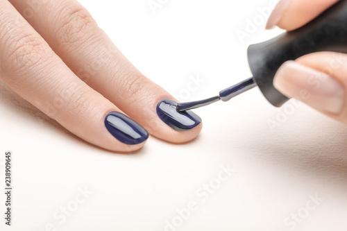 Valokuvatapetti female manicurist applying navy blue nail polish on fingernail of woman on white