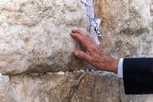 Hand Of Praying Man On The Western Wall In Jerusalem. An Old Elderly Jew Touches A Sacred Stone In Prayer. Traditional Rite For Tourists And Jews In Jerusalem Israel.