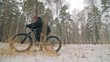 Professional extreme sportsman biker sit a fat bike in outdoors. Cyclist recline in the winter snow forest. Man walk with mountain bicycle with big tire in helmet and glasses. Slow motion in 60fps.