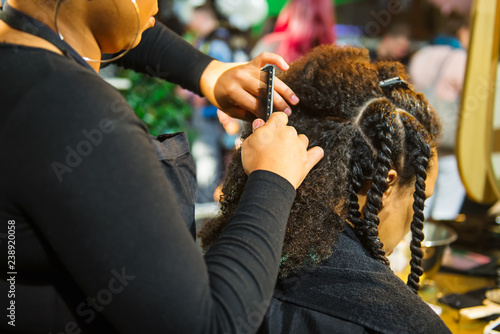 Close up african hairstylist braided hair of afro american female client in the barber salon Tablou Canvas