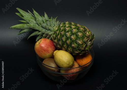 Fotografia, Obraz  Pineapple orange mandarin kiwi apple with black background in vitreous bowl