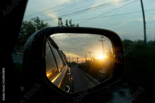 Fotografía  Side view of car mirror the backdrop in rural countryside with evening sunshine shines