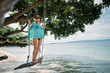 A young woman is swinging on a swing in the shade of a big tree by the sea. Girl on the beach swing on the coast of a tropical island.