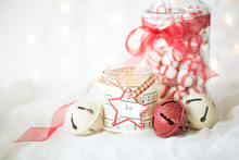 Christmas Photograph Of Red Peppermint Candies, A Jar Candle, And Red And Cream Sleigh Bells With Twinkle Lights